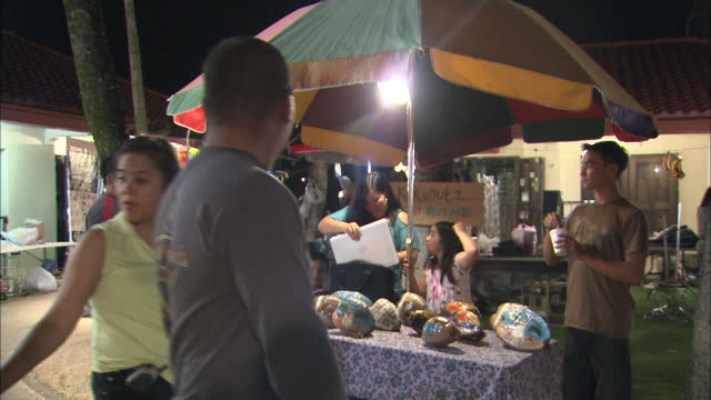 tourists and locals peruse the vendor booths at an open air market in chamorro village, guam. - isole del pacifico video stock e b–roll