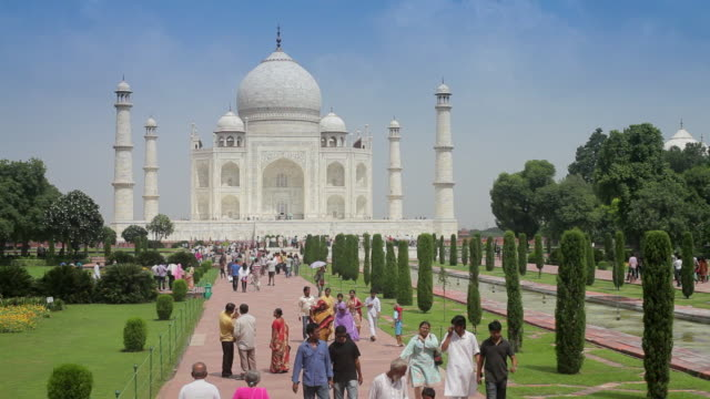 Tourists and locals stroll across a walkway near the Taj Mahal in India.