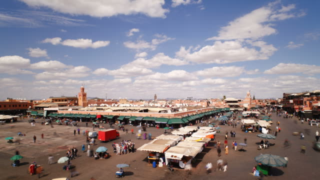 tourists and locals walk past booths at the djemaa el-fna market in marrakesh, morocco. - nachtmarkt stock-videos und b-roll-filmmaterial