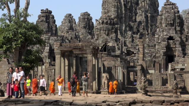 Tourists and monks at giant stone face tower of Bayon temple