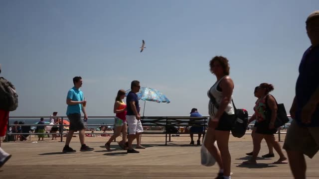 tourists and new yorkers alike enjoy the amusement parks, roller-coasters, beaches and pier of coney island on july 7 in the coney island... - pier stock videos & royalty-free footage