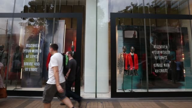 Tourists and pedestrians walk past a Chanel store on Canton Road in the Tsim Sha Tsui area of Hong Kong / A Student protestor reads a newspaper in a...