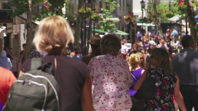 vídeos de stock e filmes b-roll de tourists and shoppers walk along main street, gibraltar - placa de nome de rua