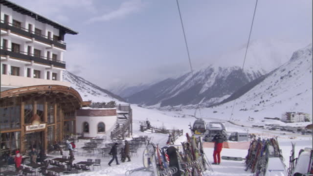 tourists and skiers enjoy a snowy resort. - stazione sciistica video stock e b–roll