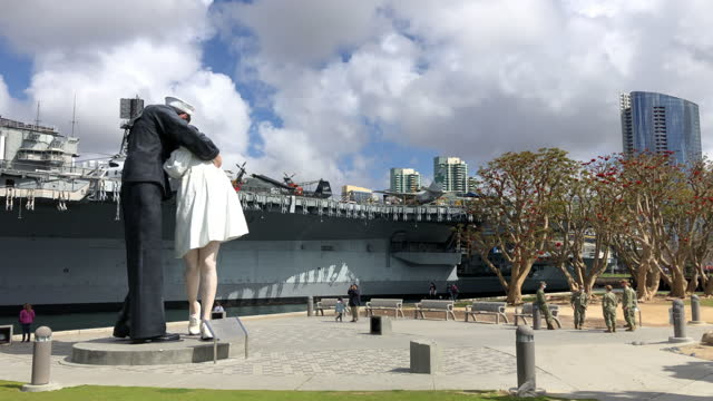 tourists and soldiers visit the sailor kissing nurse statue in front of the uss midway museum in san diego in march 2021 amid the covid-19 pandemic - war stock-videos und b-roll-filmmaterial