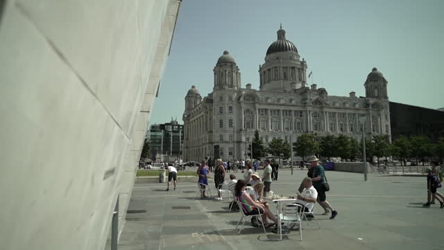 """tourists and tourist sites in liverpool, including the liver building and the beatles statue - """"bbc news"""" stock videos & royalty-free footage"""