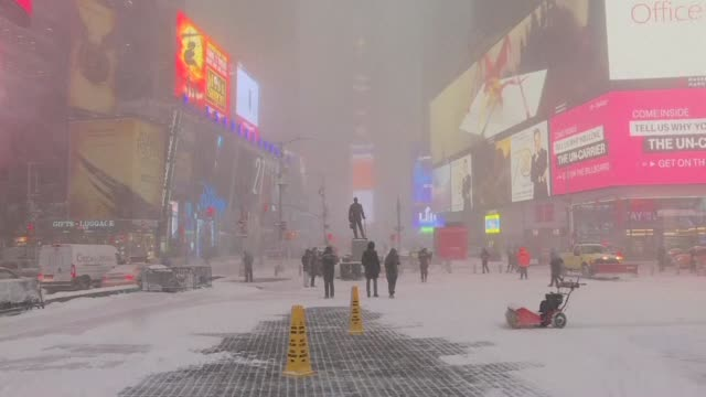 Tourists and workers grapple with the snow in New York where a storm warning has been triggered and 8 to 15 centimeters of snow are expected