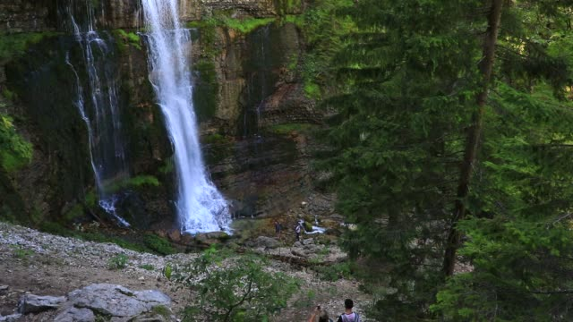 """tourists approach a waterfall at """"cirque de saint meme"""" a popular tourist site on september 3, 2020 in saint pierre d entremont, france. the 'cirque... - eco tourism stock videos & royalty-free footage"""