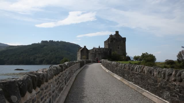 tourists are crossing the bridge to eilean donan castle at loch duich - dornie stock videos & royalty-free footage