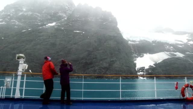 tourists are passing the cruise ship in the lemaire channel, antarctica - ponte di una nave video stock e b–roll
