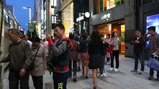 Tourists are reflected on a window of a taxfree shop in the Akihabara district of Tokyo Japan on Friday April 15 Chinese tourists wait outside Laox...