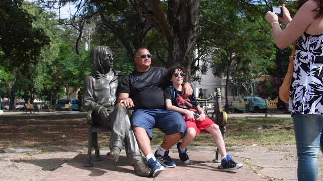 tourists are seen having their picture taken by the john lennon statue in a public park on june 22, 2018; in havana, cuba. the famous place is a... - three people stock videos & royalty-free footage