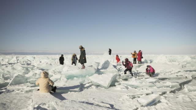 tourists are shooting selfies on the hummocks of lake baikal - gå tillsammans bildbanksvideor och videomaterial från bakom kulisserna