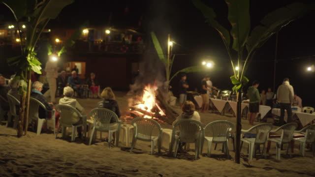 tourists around burning campfire at illuminated beach during night - luang phabang, laos - film festival stock videos & royalty-free footage