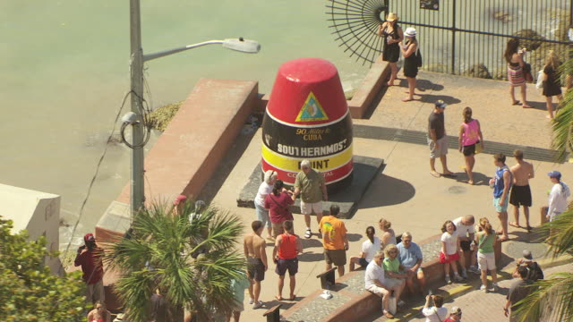 MS AERIAL ZO DS Tourists around Southernmost Point buoy and orbit around Southernmost Point / Key West, Florida, United States