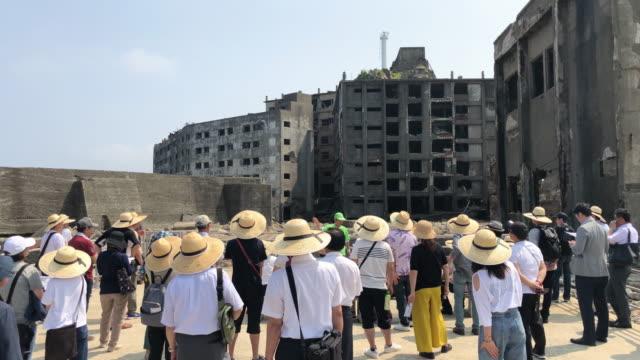 Tourists as they visit Hashima Island on June 5 2019 near Nagasaki Japan Now a popular tourist destination Hashima Island commonly called Gunkanjima...