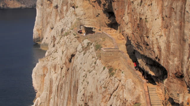 ha ws tourists ascending steps to neptune's grotto (grotta di nettuno) in limestone cliff near alghero / sardinia, italy - sardinia stock videos & royalty-free footage