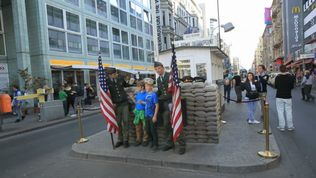 tourists at check point charlie with actors dressed as american soldiers - 敬礼点の映像素材/bロール
