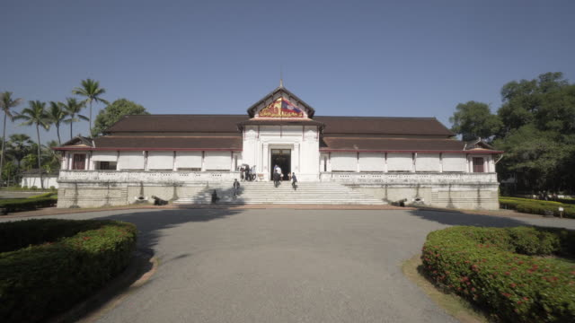 tourists at famous historic palace museum in city against clear sky on sunny day - luang phabang, laos - off the beaten path stock videos & royalty-free footage