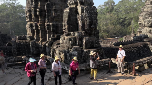Tourists at giant stone face tower of Bayon temple