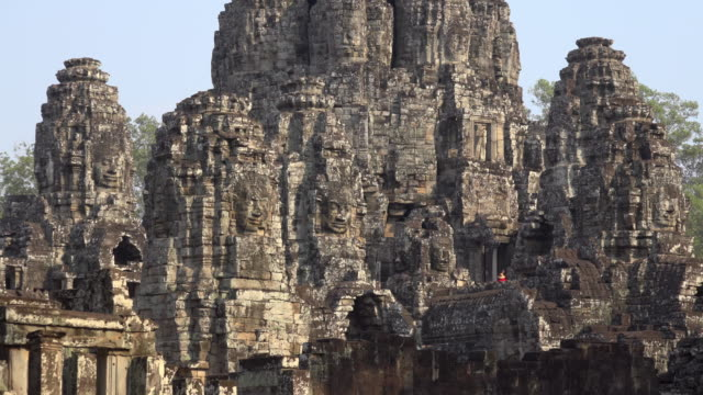 ZO / Tourists at giant stone face tower of Bayon temple
