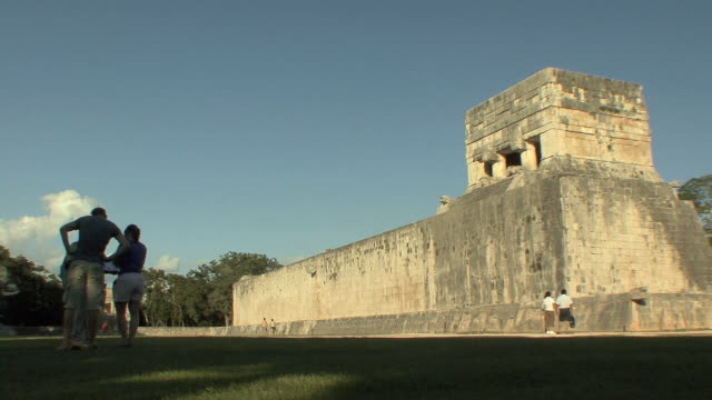 ws tourists at great ball court in front of temple of the jaguar at pre-columbian archaeological site built by maya civilization / chichen itza, yucatan, mexico - chichen itza stock videos and b-roll footage