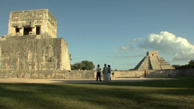ws tourists at great ball court in front of temple of the jaguar, el castillo in background, pre-columbian archaeological site built by maya civilization / chichen itza, yucatan, mexico - pre columbian stock videos & royalty-free footage