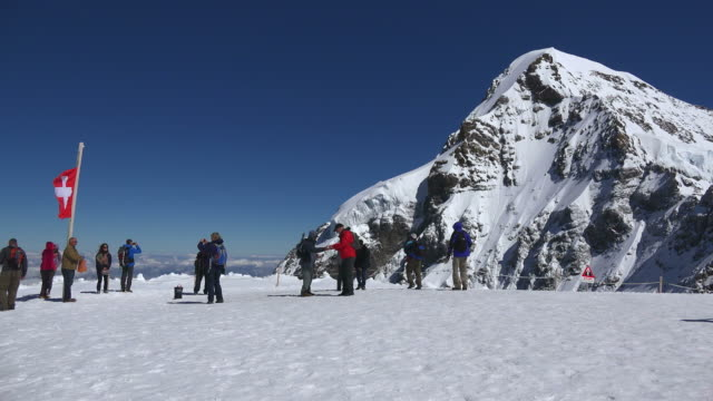 tourists at jungfraujoch, moench in background, bernese oberland, canton of bern, switzerland - berg jungfrau stock-videos und b-roll-filmmaterial