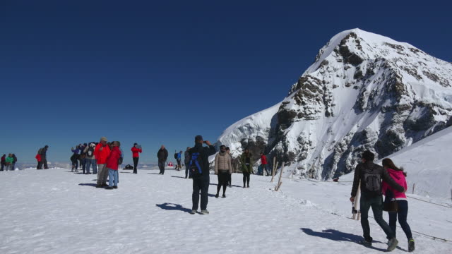 Tourists at Jungfraujoch, Moench in background, Bernese Oberland, Canton of Bern, Switzerland