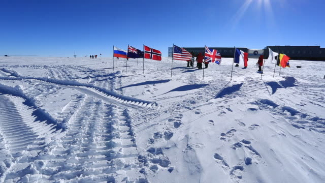 tourists at magnetic south pole (unrecognizable) with amundsen-scott south pole station behind - south pole stock videos & royalty-free footage