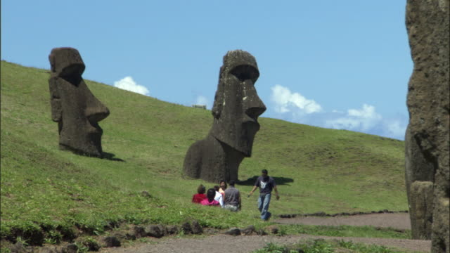 ws tourists at moai statues on green hill / easter island, chile - stone object stock videos & royalty-free footage