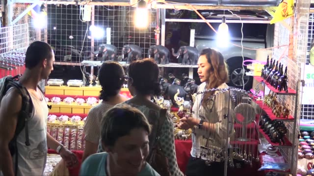 vídeos de stock e filmes b-roll de tourists at one of the stalls in the night market in chang klan road in the eastern part of chiang mai. the market, which operates every evening, is... - mercado noturno