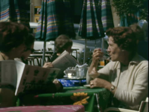 montage tourists at outdoor cafe, one eating ice cream and the other reading an ice cream brochure / florence, italy - 1966 stock-videos und b-roll-filmmaterial
