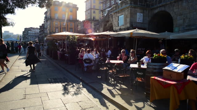 tourists at sidewalk cafe and footpath by buildings in city on sunny day - porto, portugal - lens flare stock videos & royalty-free footage
