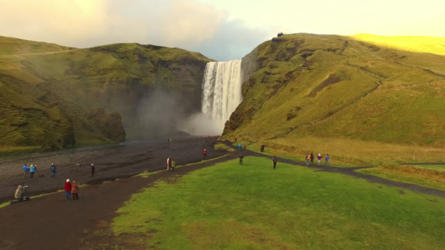 AERIAL Tourists at Skogafoss waterfall in Iceland