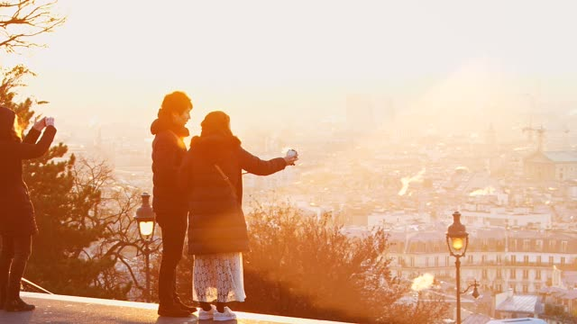Tourists at sunrise in Montmartre over Paris rooftop France