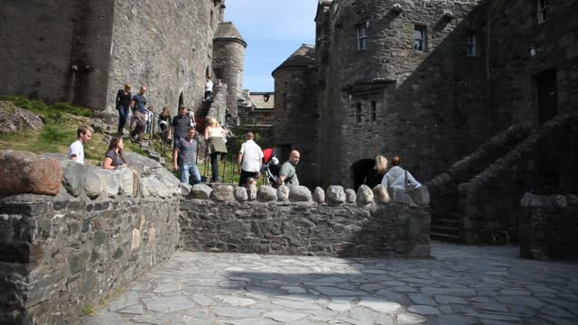 tourists at the eilean donan castle on an island in loch duich is only accessible via a stone bridge - dornie stock videos & royalty-free footage