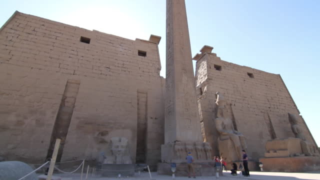 tourists at the entrance of luxor temple / exterior wide shot of the first pylon with tilt of the red granite obelisk - igneous stock videos & royalty-free footage