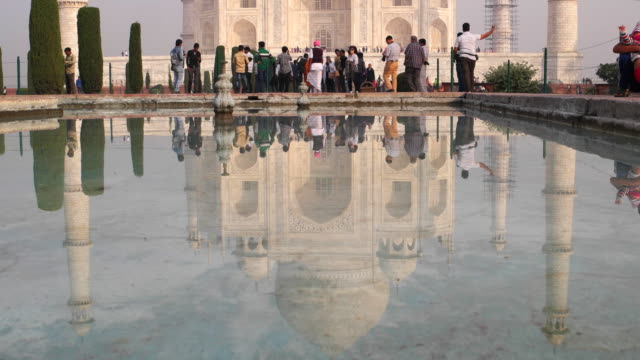 vídeos de stock e filmes b-roll de ls tourists at the taj mahal with their reflection in the blue waters - taj mahal
