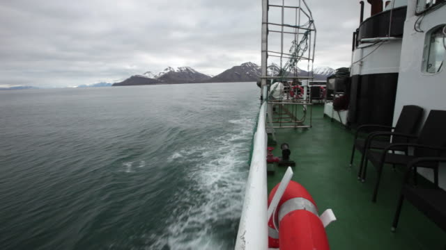 Tourists boat sailing on Isfjorden, the second longest fjord in the Norwegian archipelago of Svalbard; beautiful mountains covered by snow are visible in the back