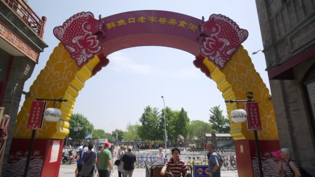 tourists by arch decoration with non-westerns script against sky during sunny day - beijing, china - natural arch stock videos & royalty-free footage