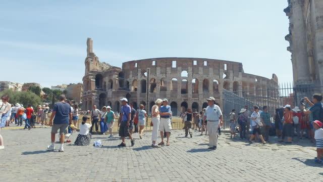 vídeos de stock e filmes b-roll de tourists by the coliseum of rome during summer vacations - roma itália
