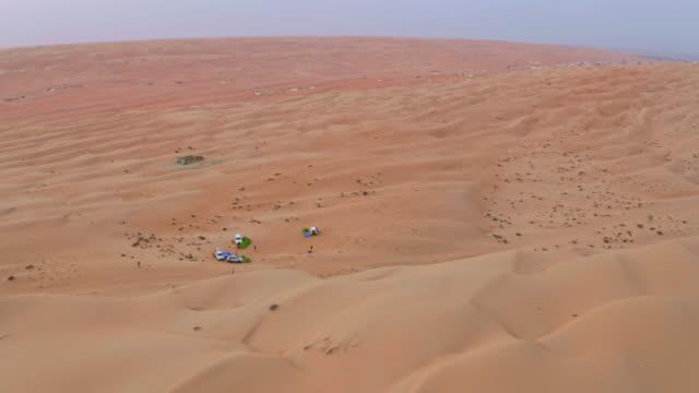 vídeos y material grabado en eventos de stock de turistas aéreos acampar en el desierto en omán - tienda de campaña