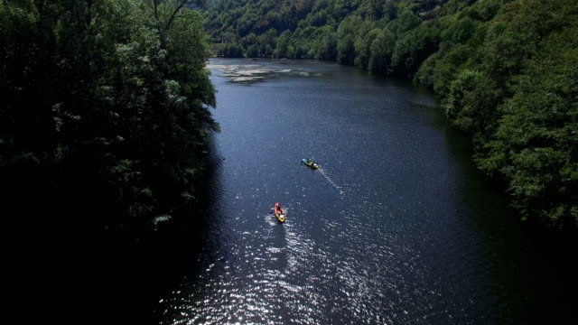 Tourists canoeing on the tree lined Lot river near Grand Vabre, Aveyron, France