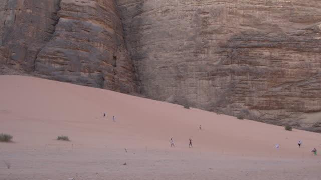tourists climbing a sand dune in wadi rum desert, jordan - sandstone stock videos & royalty-free footage