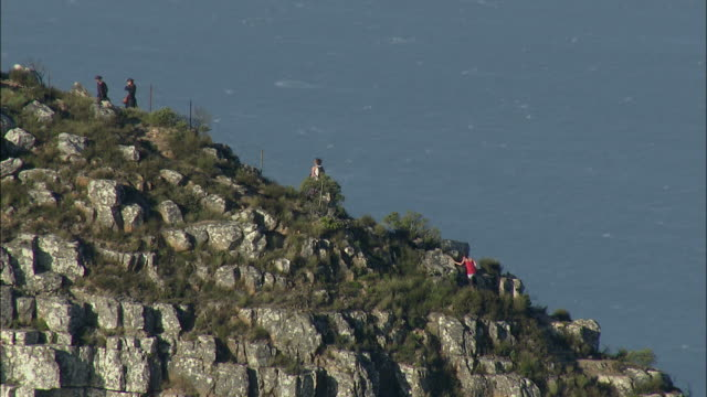 low aerial tourists climbing lion's head, cape town, western cape, south africa - ライオンズヘッド点の映像素材/bロール