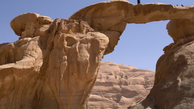 tourists climbing on the natural arch burdah rock bridge in wadi rum desert, jordan - sandstone stock videos & royalty-free footage