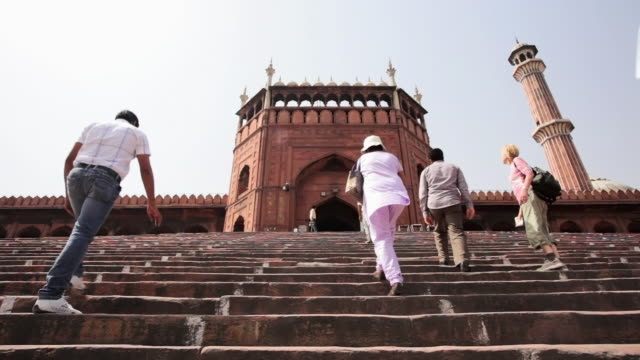 LS Tourists climbing steps into the Jama Masjid, a Muslim mosque / Delhi, Punjab, India