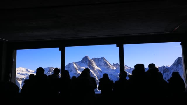 tourists contemplate a mountain landscape in jungfraujoch area highest railway station in europe in the bernese alps mountain range on december 3... - european alps stock videos & royalty-free footage