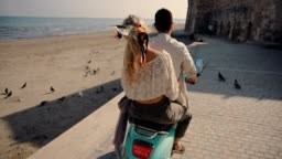 Tourists couple on summer vacations riding scooter on Mediterranean island